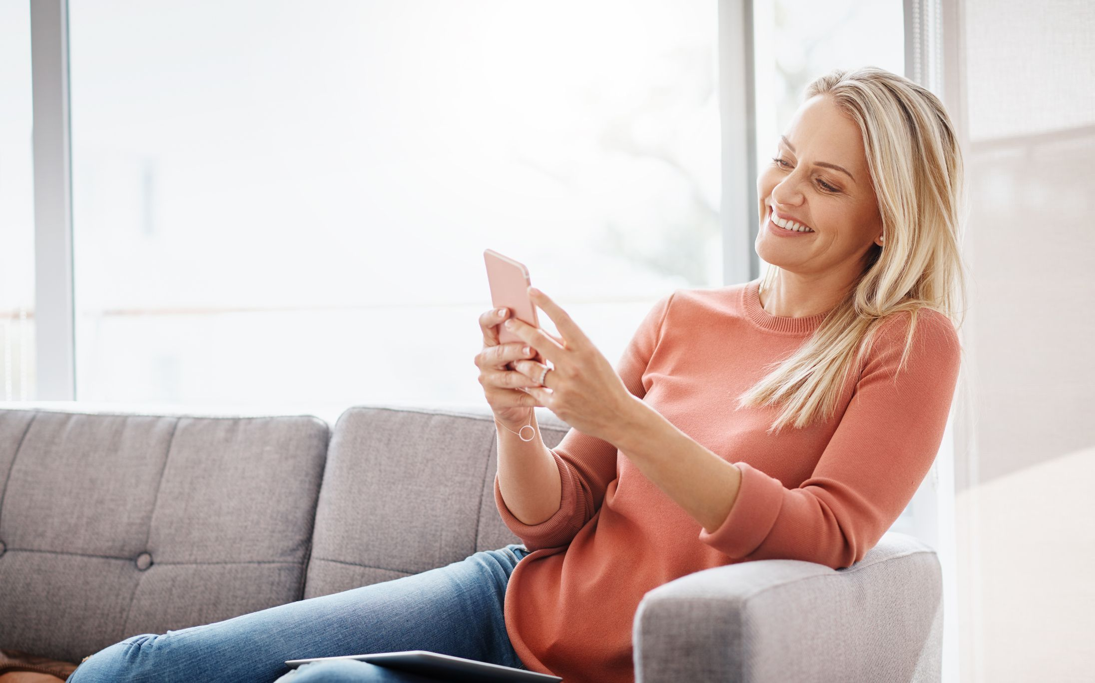 a woman sitting at home on mobile phone