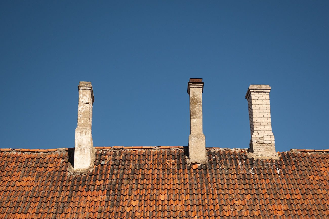 Close Up of Red Roof Tiles and Two Chimneys