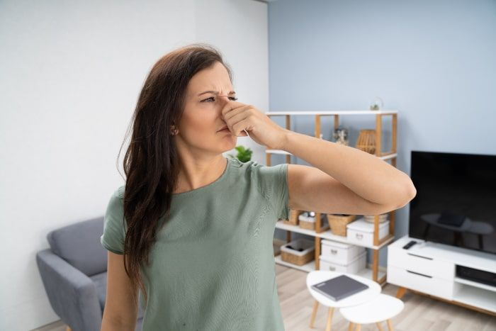 Woman Holding Nose Because of Bad Crawlspace Smell
