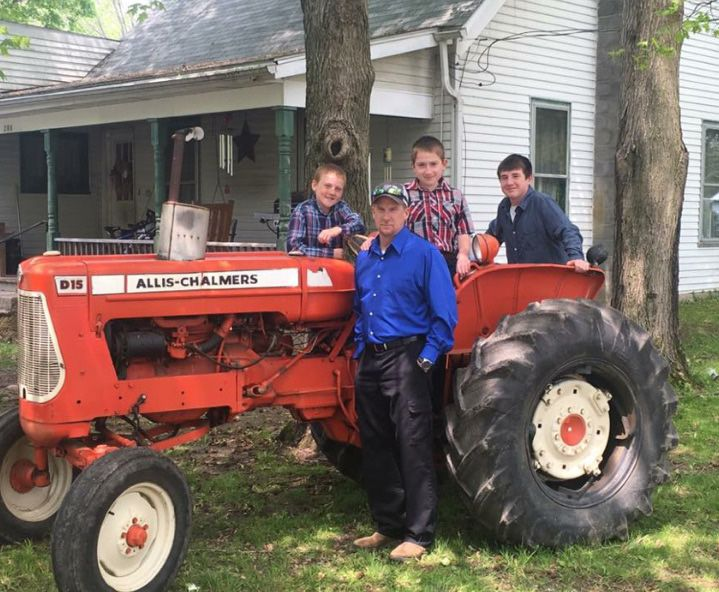 Roy's son (standing) Brent Dick and grandsons (from left) Braxton, Cole and Mason, on the day of the funeral. In honor of their loved one, they drove the tractor behind the hearse to the cemetery.