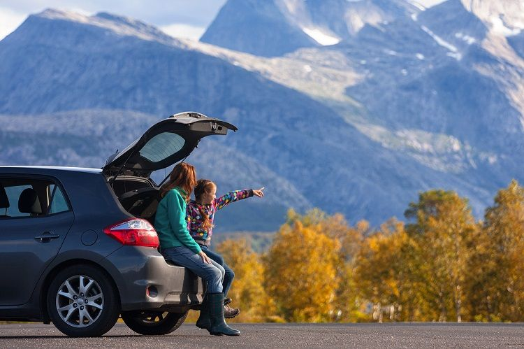 Mom and Daughter Sitting in the back of Car with Mountain Scenery