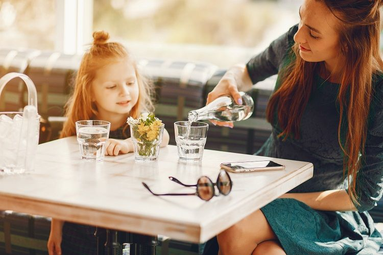 Mom and Daughter at Restaurant Table Drinking Water