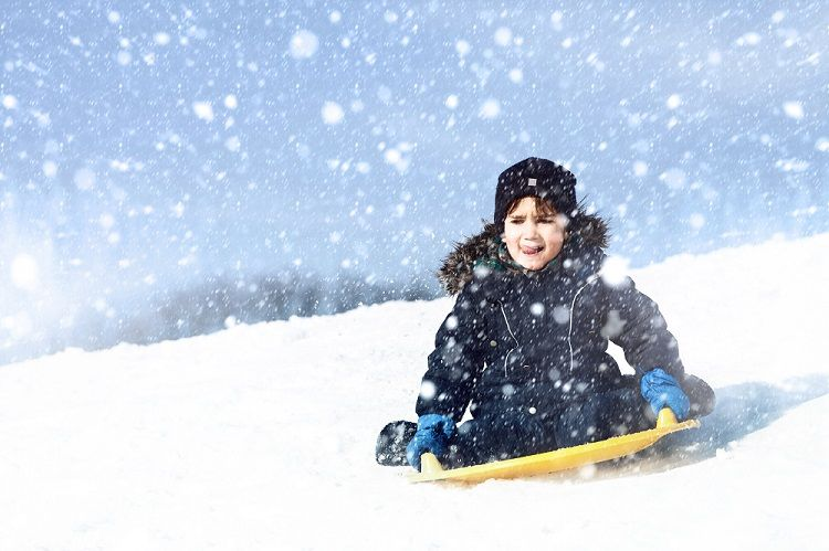 Child sledding down hill