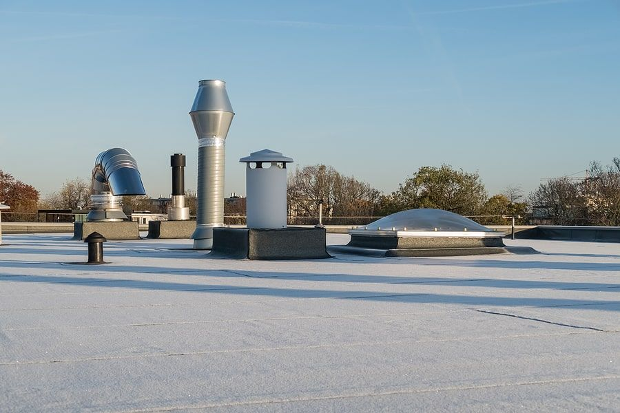 The top of a roof with silver power poles