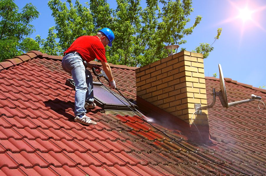 Man pressure cleaning to remove moss from a roof