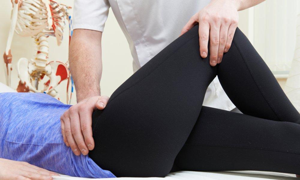 Doctor examines patient's hip