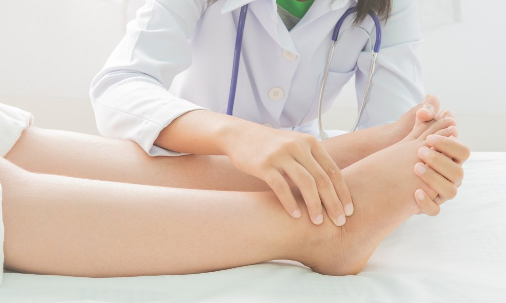 Doctor examines patient's ankle