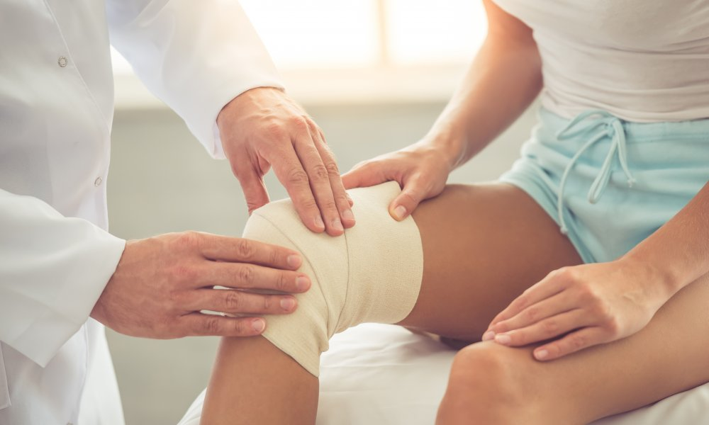 male doctor examining female patient's bandaged knee