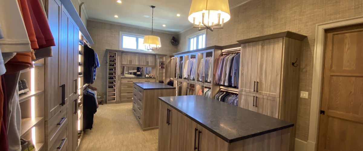 a closet with an island in the middle of a room