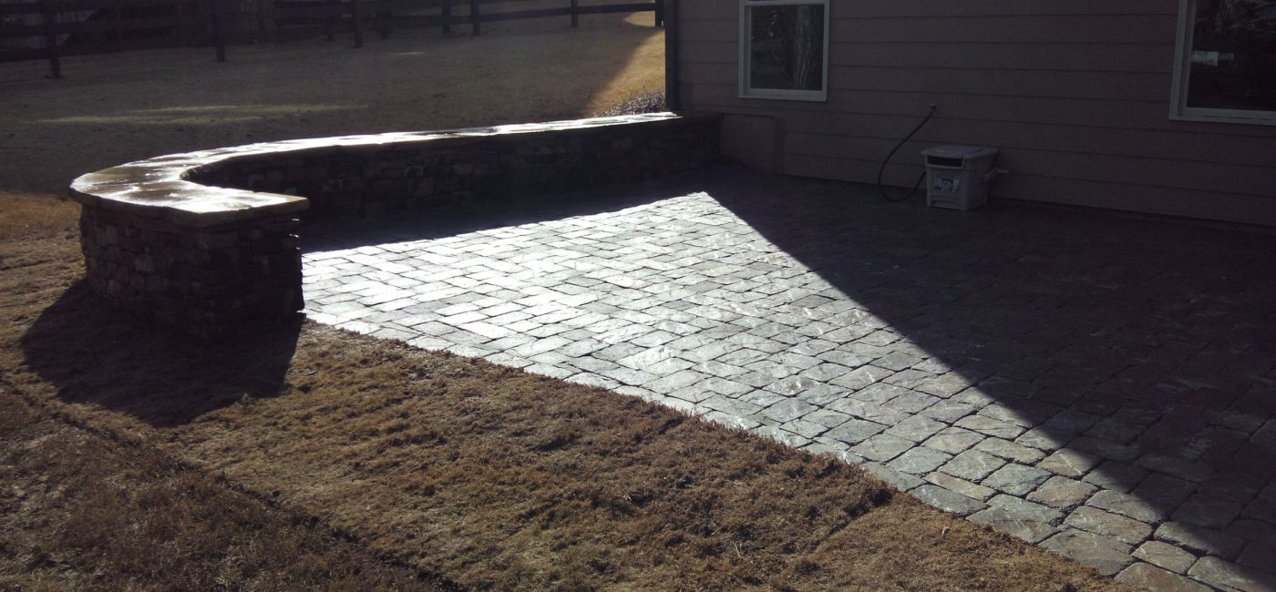 Paver patio with short stone wall and cap.