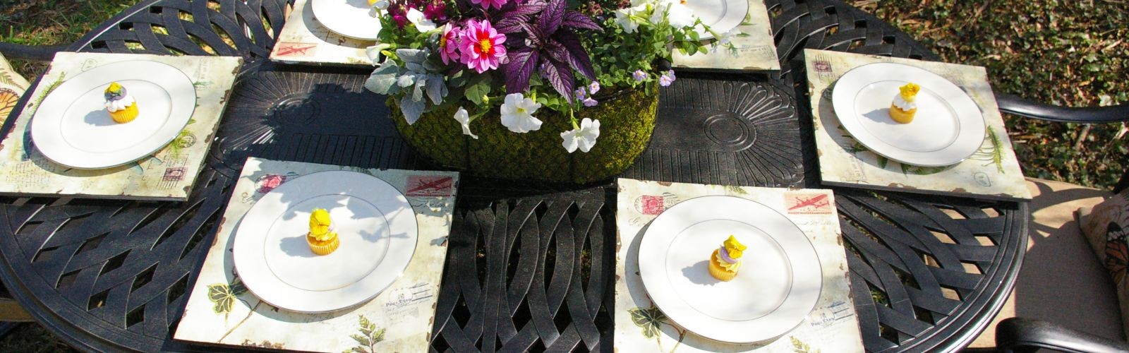 Outdoor garden party with flower centerpiece and plants with desserts