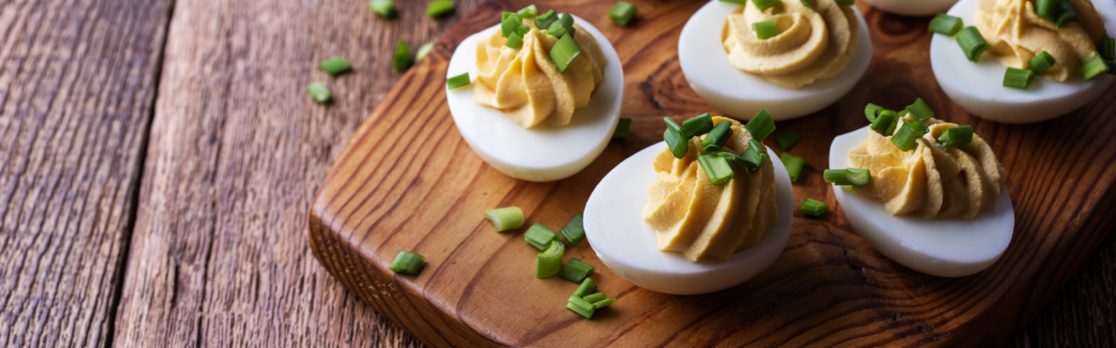 a plate of deviled eggs on a wooden table