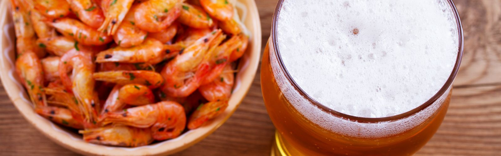 A bowl of shrimp and a glass of beer