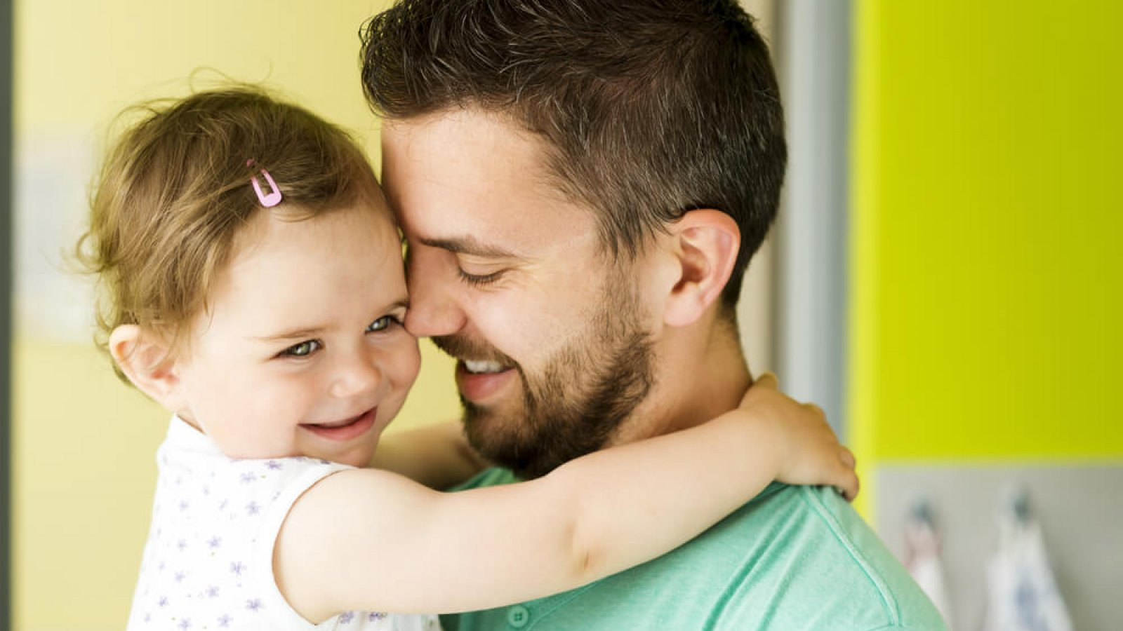 Image of father holding young daughter