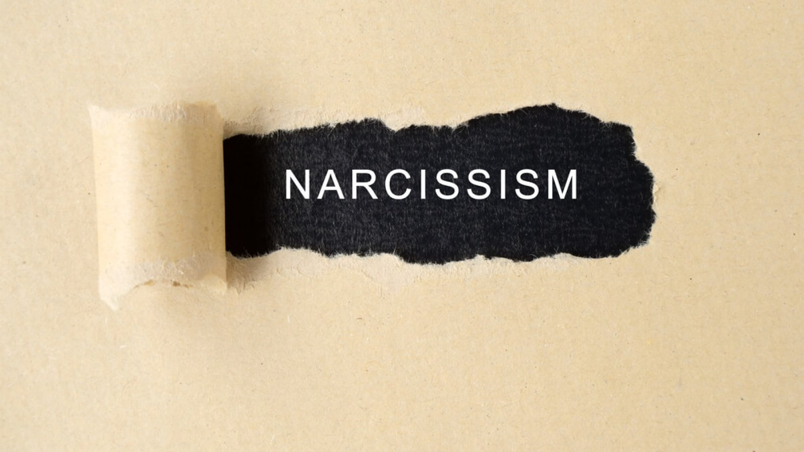 The word narcissism beneath a torn piece of paper