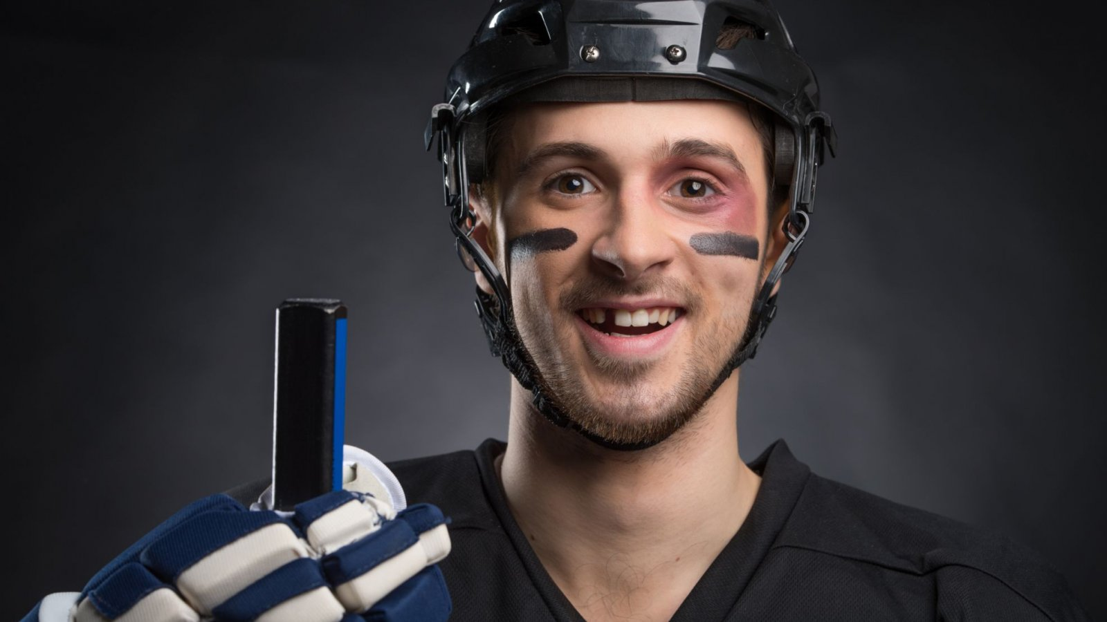 hockey player smiling holding a hockey stick