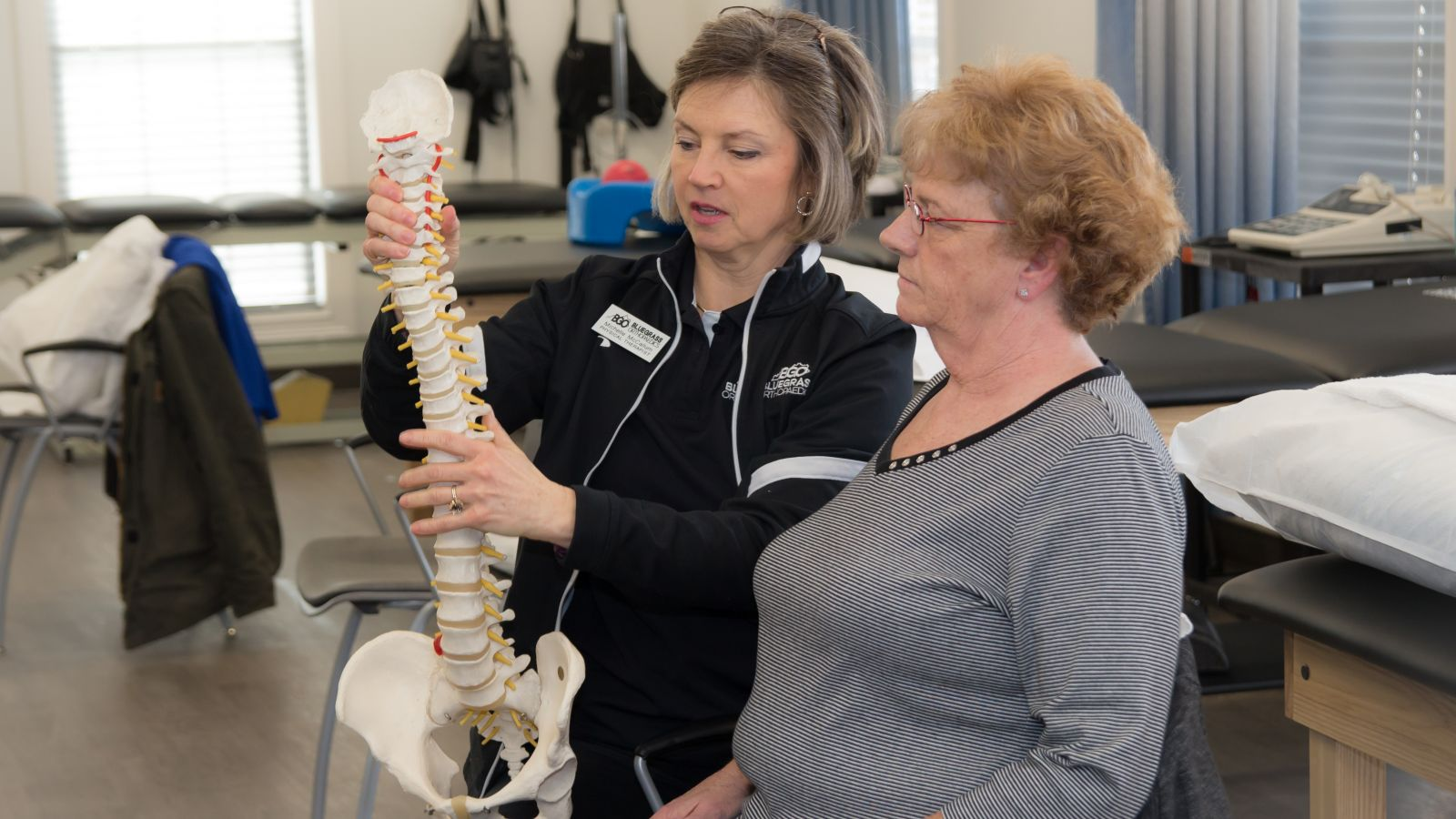 a woman assisting patients with physical therapy