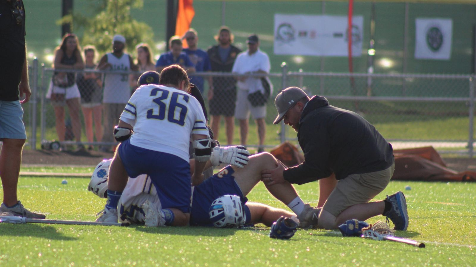an athletic trainer helping an injured player on a field