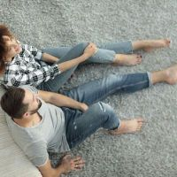Man and woman sitting on carpet