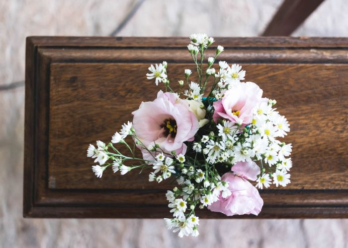 a vase filled with flowers sitting on top of a wooden table